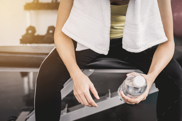 Fitness woman holding a bottle of water after work out - Stock Photo - Images