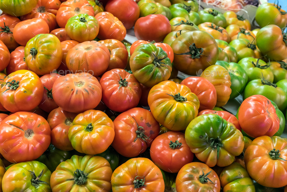Red and green tomatoes for sale at a market  - Stock Photo - Images