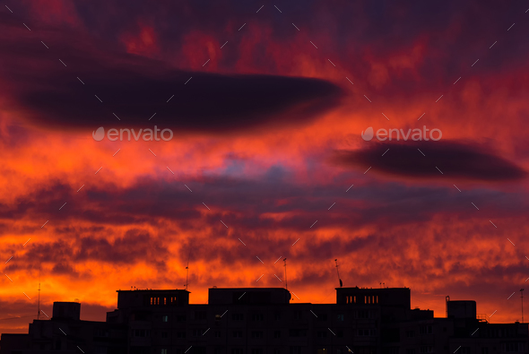 Sunrise in the city. Silhouette of residential apartments against vibrant red sky - Stock Photo - Images
