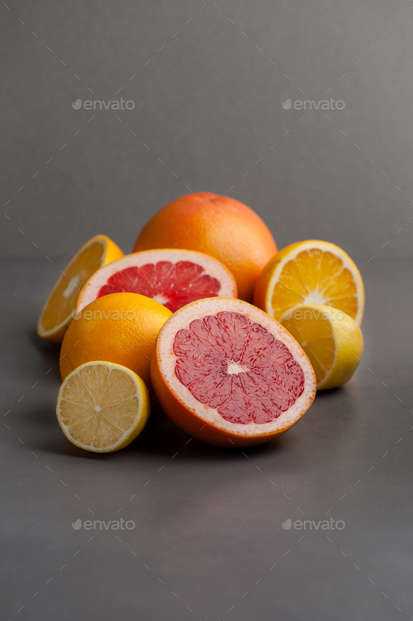 Grapefruits, oranges and lemons on a gray background. - Stock Photo - Images
