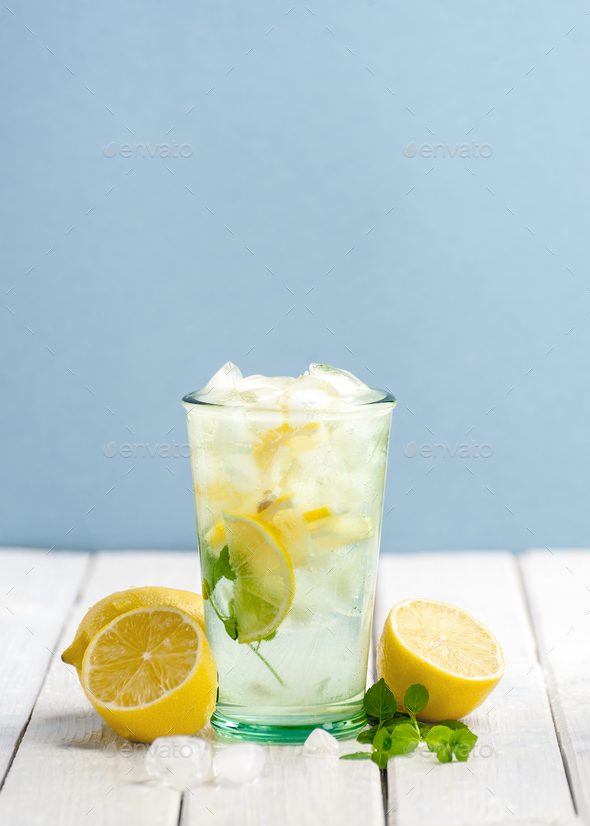 Cold lemonade and fresh lemons on a white wooden table on a blue - Stock Photo - Images