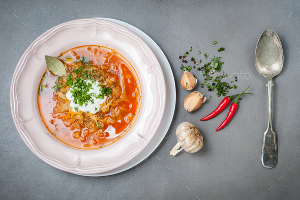 Cabbage soup with tomatoes in a plate and an old vintage spoon o - Stock Photo - Images