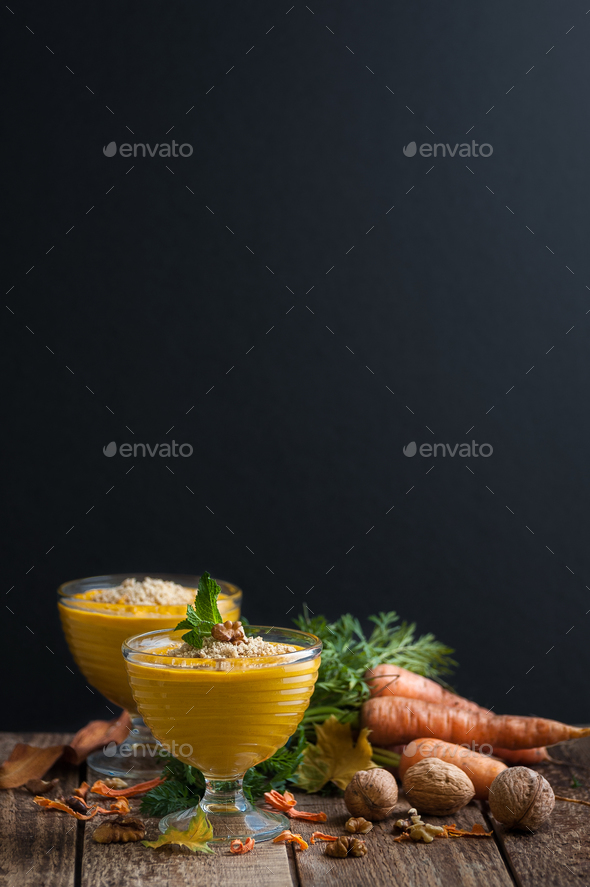 Carrot pudding with crushed nuts is served on a black background - Stock Photo - Images