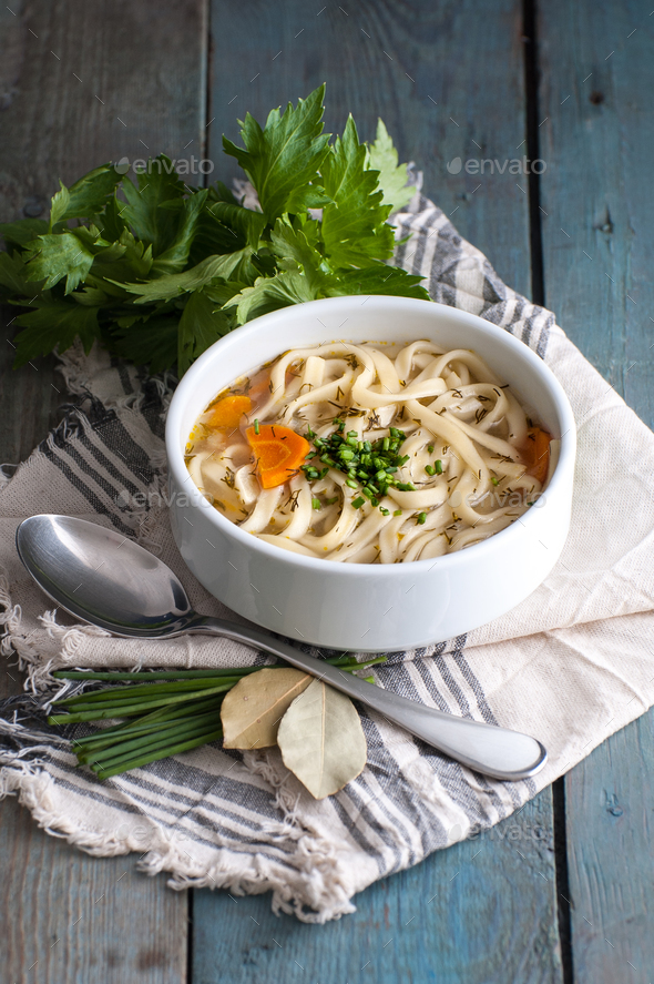 Homemade chicken soup with homemade noodles on an old wooden tab - Stock Photo - Images