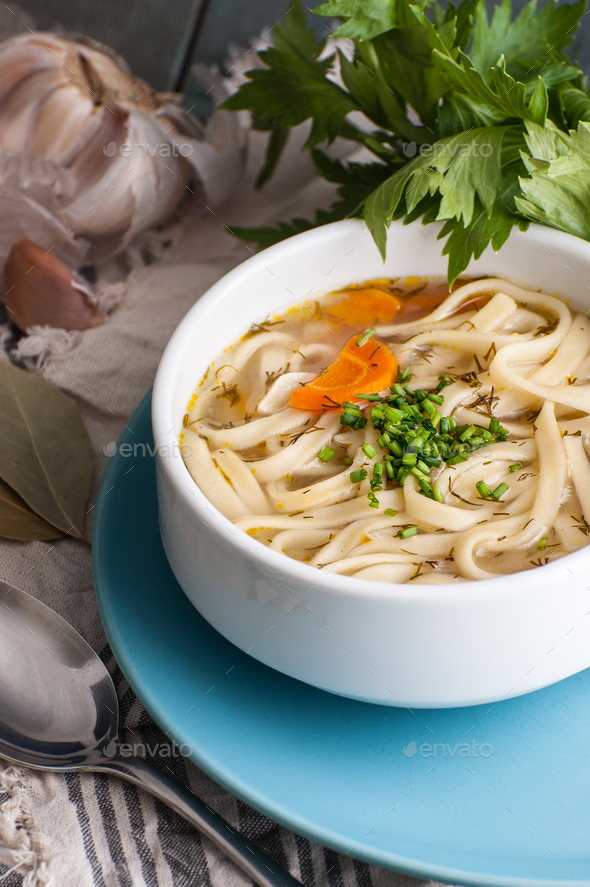 Chicken soup with homemade noodles on an old wooden table. - Stock Photo - Images