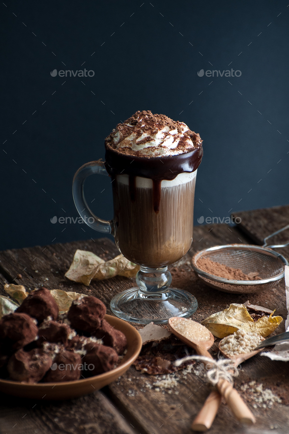 Coffee with cream and sloppy truffles on an old wooden table. - Stock Photo - Images