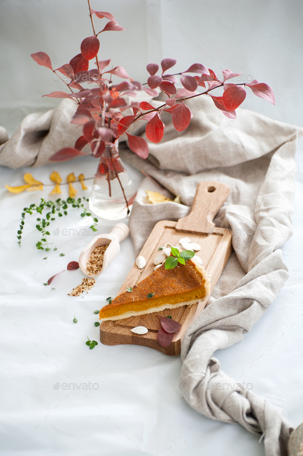 A piece of pumpkin pie on a wooden board. - Stock Photo - Images