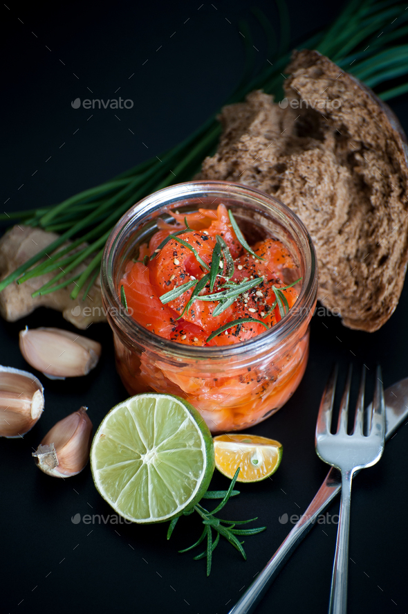 Marinated salmon with rosemary and spicy pepper in a glass jar. - Stock Photo - Images