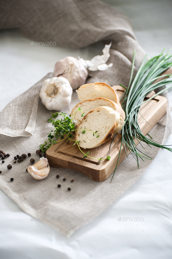 Three pieces of freshly baked baguette on a wooden board and fre - Stock Photo - Images