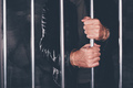 Handcuffed man behind prison bars - PhotoDune Item for Sale