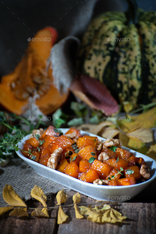 A tender baked pumpkin with honey, nuts and thyme leaves. Shooti - Stock Photo - Images
