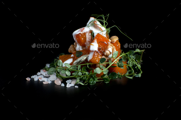 Baked pumpkin with nuts and thyme leaves with cream sauce. Shoot - Stock Photo - Images