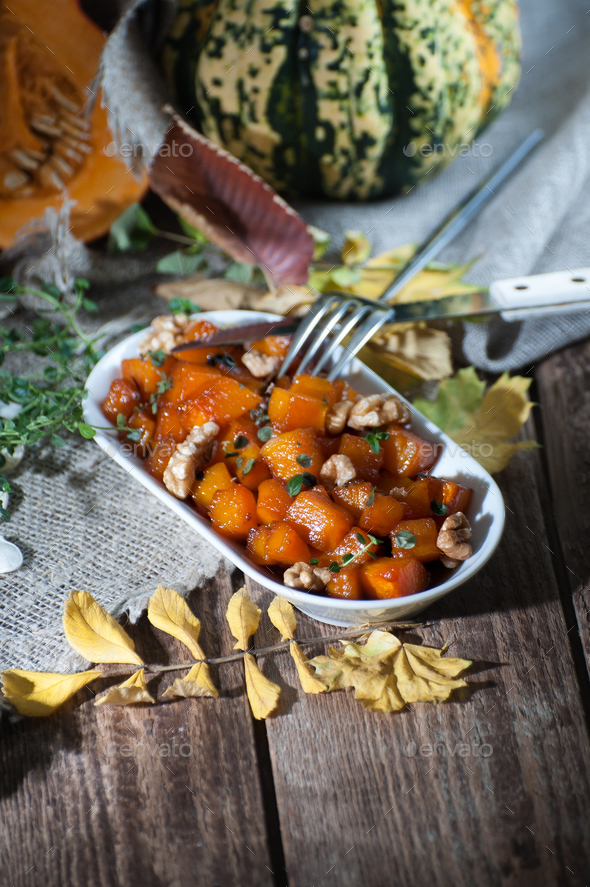 Baked pumpkin with honey, nuts and thyme leaves. Shooting in dar - Stock Photo - Images