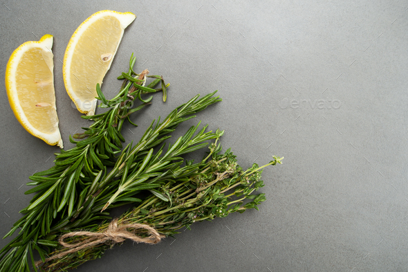 Fresh rosemary, thyme and two slices of lemon on a gray stone ta - Stock Photo - Images