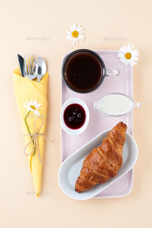 Breakfast consisting of black coffee, milk and a croissant with - Stock Photo - Images