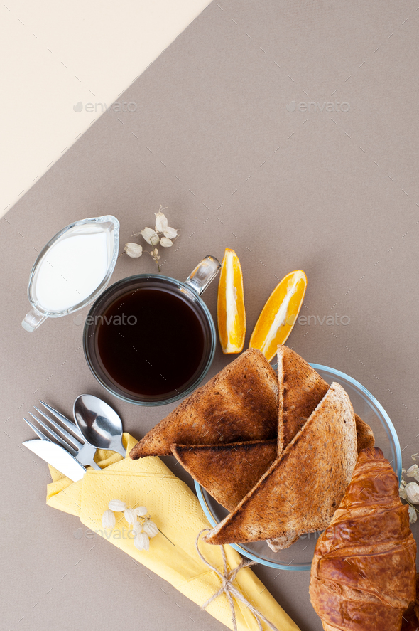 Black coffee, cream, fresh croissants and toasts are served on a - Stock Photo - Images