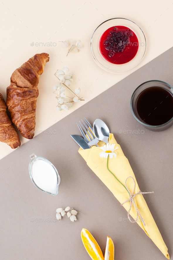 Black coffee, milk, croissants, jam and fresh fruit on a light y - Stock Photo - Images