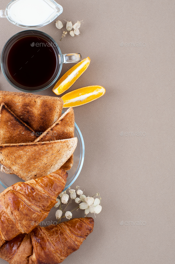Black coffee, milk, fresh croissants and toasts on the side on a - Stock Photo - Images