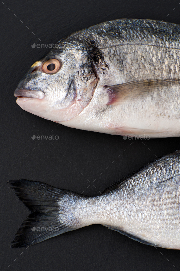 Two pieces of fresh Dorado fish on a black stone background. - Stock Photo - Images
