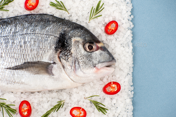 Fresh Dorado fish with rosemary and chili pepper on a salt cushi - Stock Photo - Images