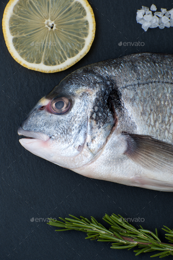 Fresh Dorado fish, lemon, rosemary and salt close-up on a black - Stock Photo - Images