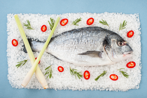 Dorado fish on a salt cushion with rosemary, chili pepper and le - Stock Photo - Images