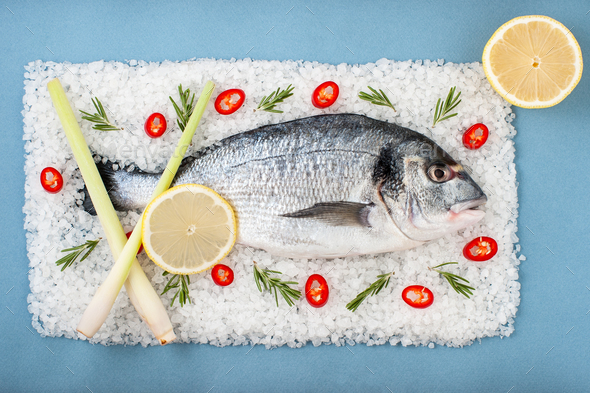 Fresh Dorado Fish with rosemary, chili pepper and lemon on a sal - Stock Photo - Images