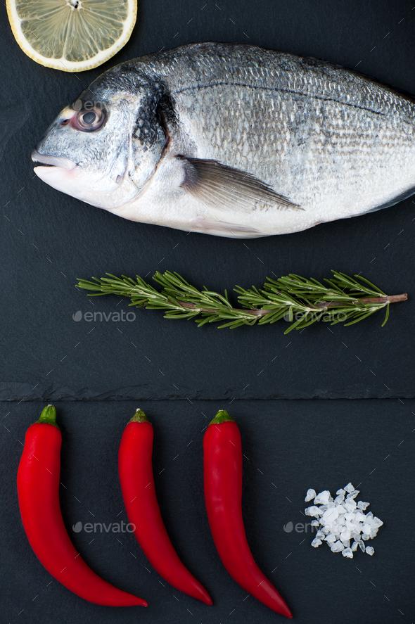 Fresh Dorado fish, lemon, chili pepper, rosemary and salt on a b - Stock Photo - Images