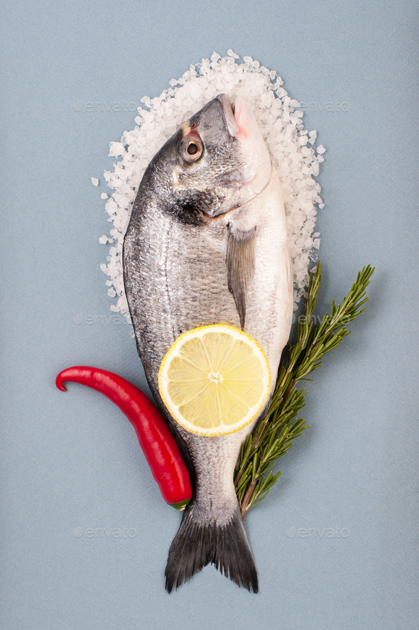 Dorado fish, large sea salt, chili, lemon and rosemary on a ligh - Stock Photo - Images