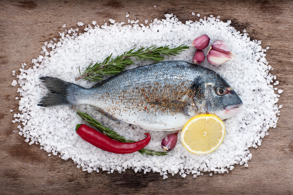 Dorado fish lies on a large sea salt with fresh garlic, chili, l - Stock Photo - Images
