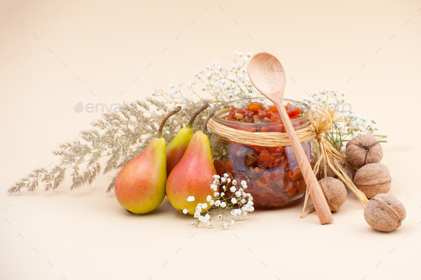 Still life with pear jam, pears, dried herbs and walnuts on a li - Stock Photo - Images