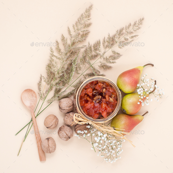 Still life with a pear jam, pears and walnuts on a light beige b - Stock Photo - Images