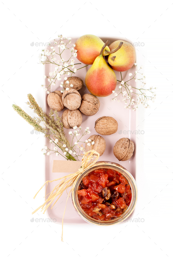 Pear jam, pears and walnuts are served on a light pink tray on a - Stock Photo - Images
