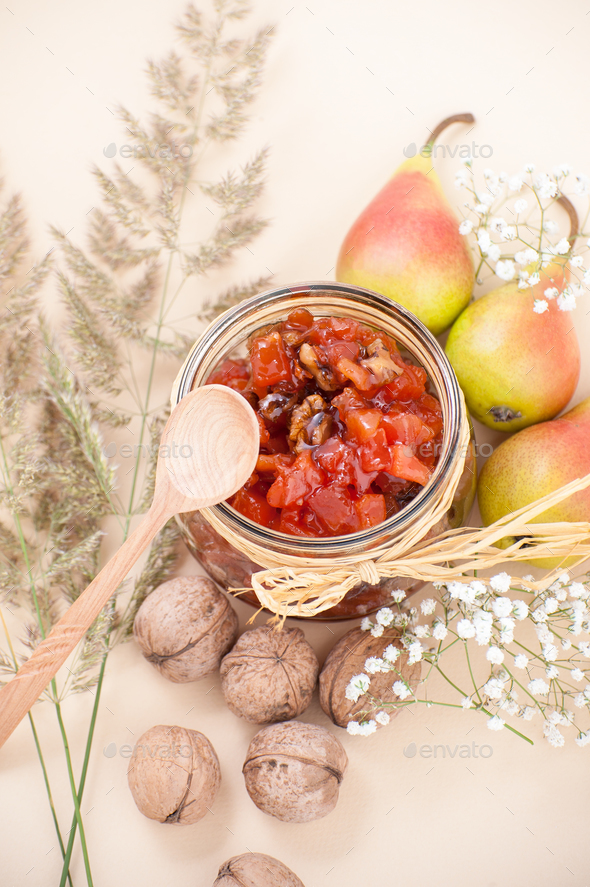 Pear jam in a jar on a light yellow pastel background. - Stock Photo - Images