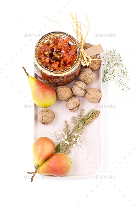 Pear jam, pears and walnuts on a light pink tray on a white back - Stock Photo - Images