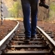 A Man with DSLR Camera Walks Down Train Tracks on a Background Autumn Forest. A Man Departs From the - VideoHive Item for Sale
