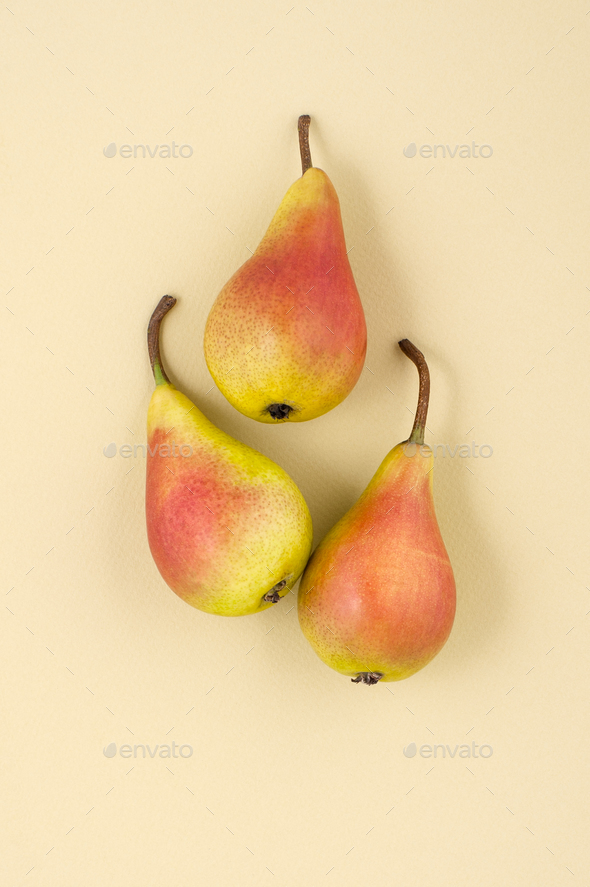 Three ripe pears on a light yellow pastel background. - Stock Photo - Images