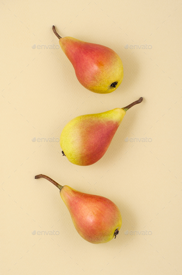 Three ripe juicy pears on a light yellow pastel background. - Stock Photo - Images