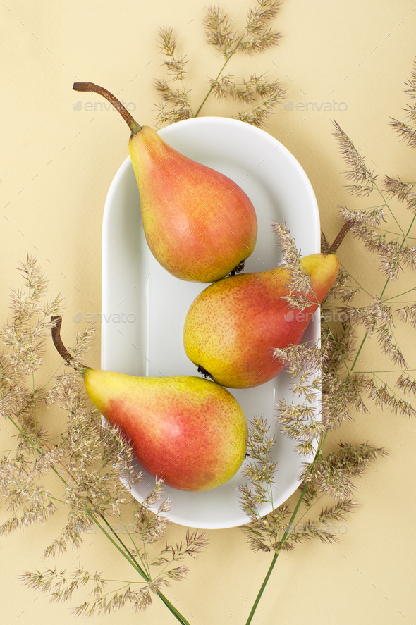 Three ripe pears on a white plate on a light yellow pastel backg - Stock Photo - Images