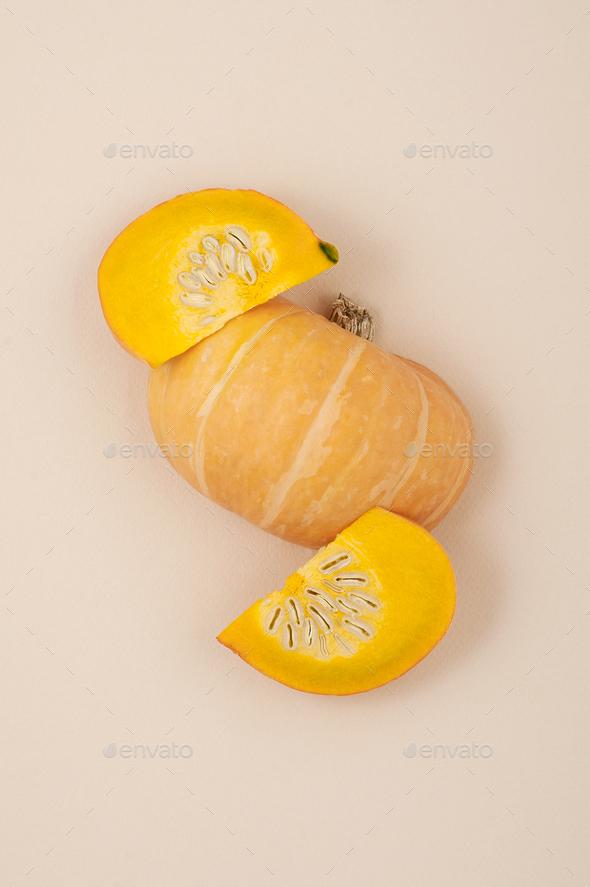 Fresh orange cut pumpkin on a light beige pastel background clos - Stock Photo - Images