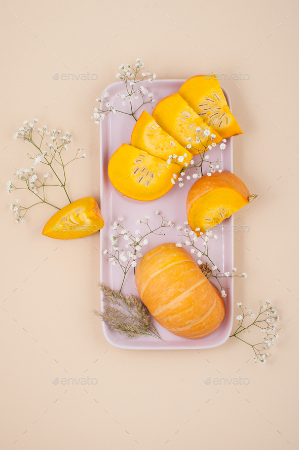 Slices of fresh young pumpkin on a rectangular pink plate on an - Stock Photo - Images