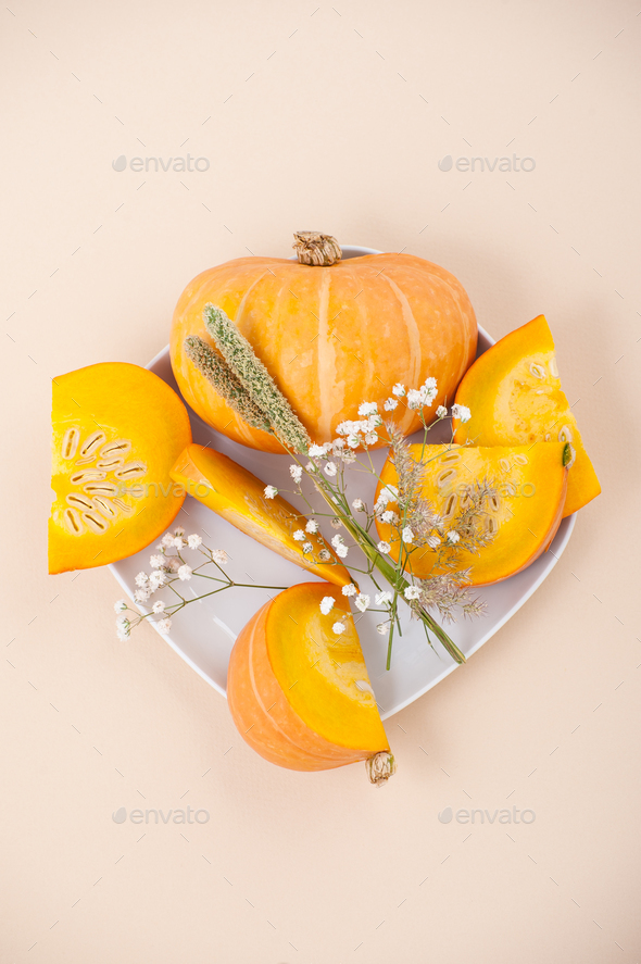 Slices of fresh orange pumpkin and dried flowers on a white plat - Stock Photo - Images