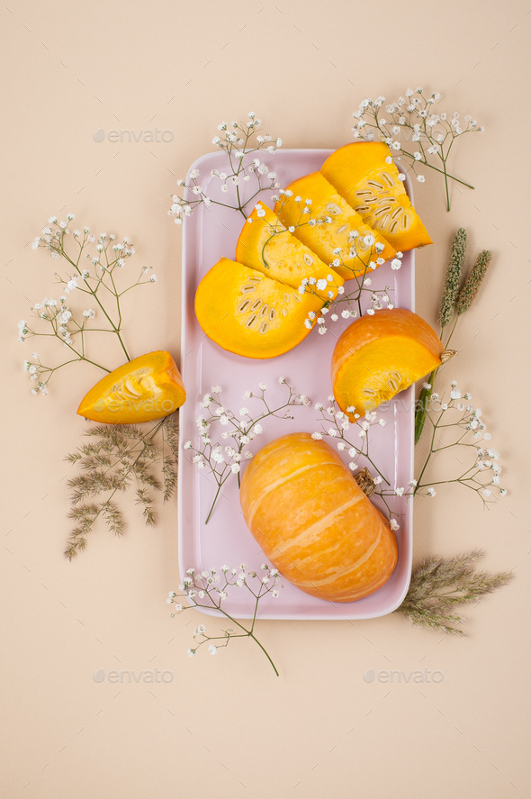 Slices of fresh pumpkin and dried white flowers on a pink plate - Stock Photo - Images