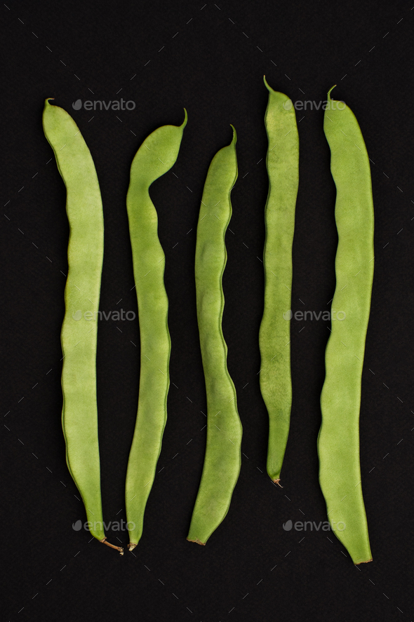 String of fresh young beans on a black textural background. - Stock Photo - Images