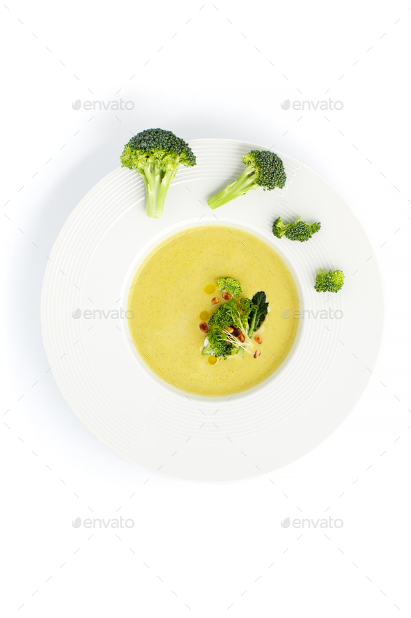 White plate with cream of broccoli soup, served with pine nuts o - Stock Photo - Images