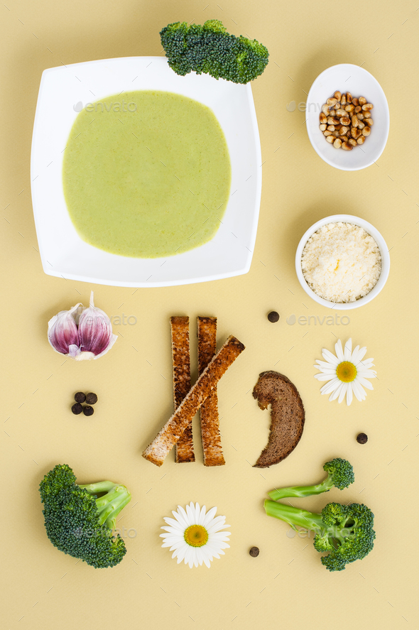 Cream soup of broccoli in a white plate and ingredients on a yel - Stock Photo - Images