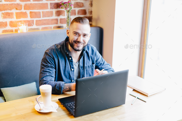 Attractive man smiling in a cafe. Working environment. - Stock Photo - Images