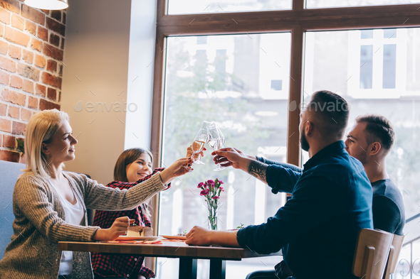 Four friends sitting together with glasses of champagne. - Stock Photo - Images