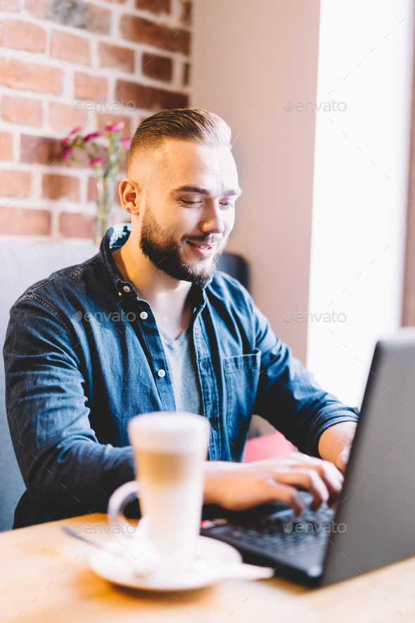 Portrait of a man sitting with laptop - Stock Photo - Images