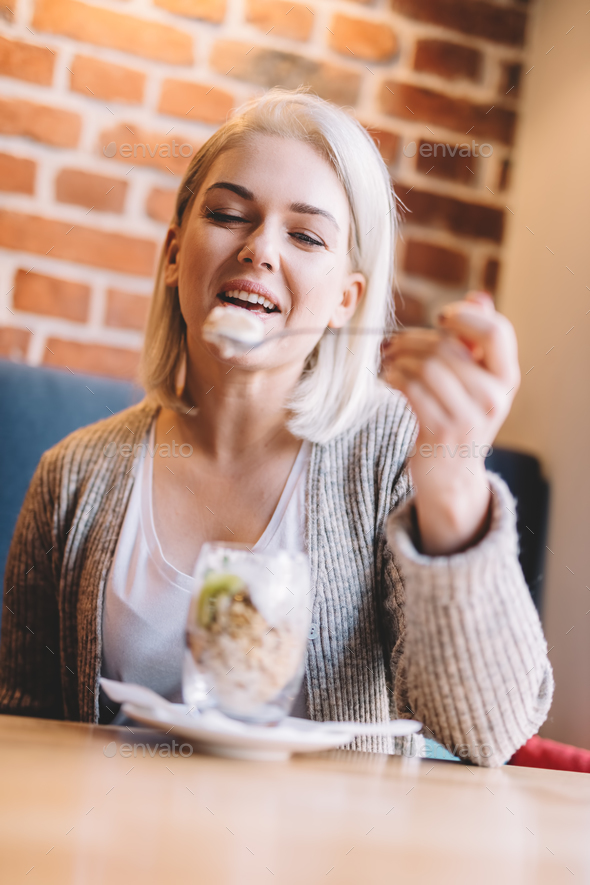 Woman eating fit meal with fruits and oats in a cafe. - Stock Photo - Images